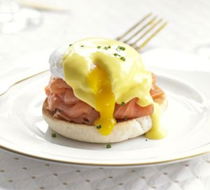 Eggs Benedict covered in hollandaise saice