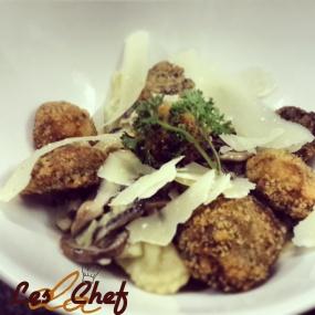 Pea puree stuffed ravioli with deep fried mushrooms, parmesan shavings in  creamy garlic cheese sauce